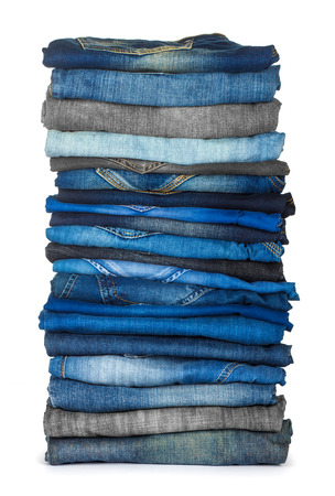 slacks: high stack of various shades of blue jeans on a white background Stock Photo