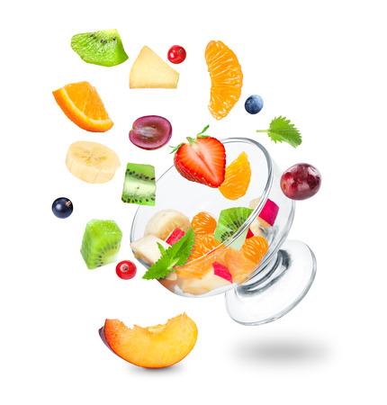 mosca: deliciosa ensalada de fruta fresca que cae sobre un fondo blanco Foto de archivo