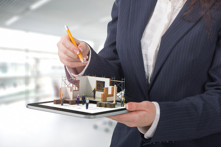 architector: Project concept. Demonstration of an architectural project. Man draws a house project on the tablet.