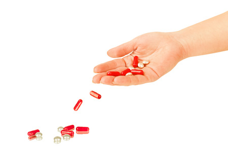 falling out: pills falling out of hand on white background