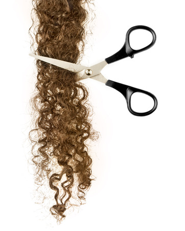 Scissors and lock of hair on a white photo