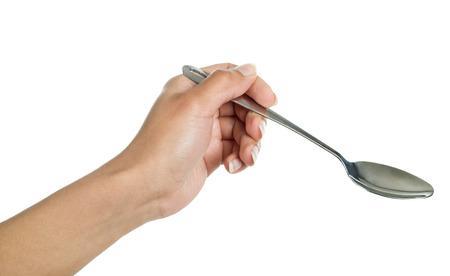 cuchara: cuchara en la mano sobre un fondo blanco Foto de archivo
