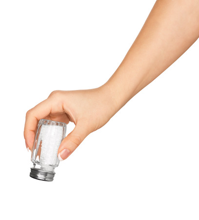 hand holding a glass saltcellar with salt isolated on a white background photo