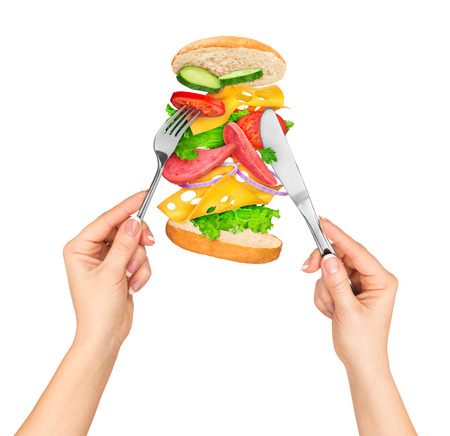 prick: a knife and fork prick sandwich with ingredients in the air on a white background Stock Photo