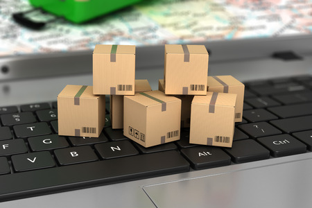 logistics: Shipping delivery and logistics technology business industrial concept: macro view of heap of stacked corrugated cardboard package boxes on computer PC laptop notebook keyboard with selective focus Stock Photo