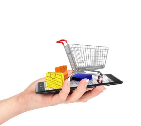 famale: Online shop concept. Female hand holding a phone on which stands empty shopping cart and colorful package. E-commerce.
