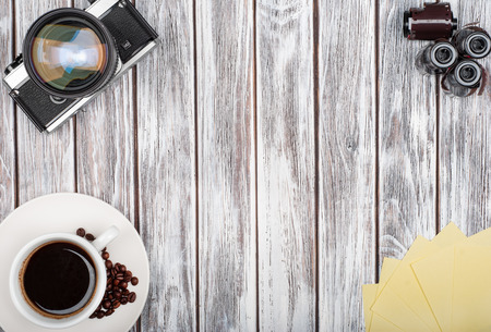 vintage film cameras and films with coffee on a white wooden background