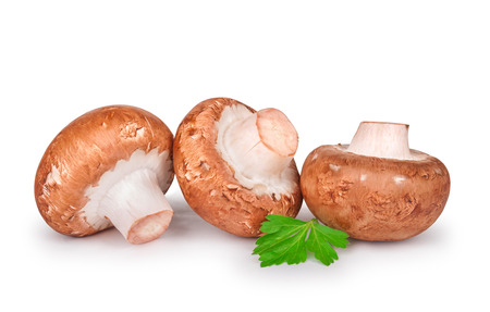 Three fresh champignons with parsley isolated on white background Stock Photo