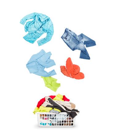 바구니에 세탁 및 흰색 배경에 고립 떨어지는 옷