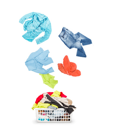 lavanderia: Lavandería en una canasta y la caída de la ropa aislada sobre un fondo blanco