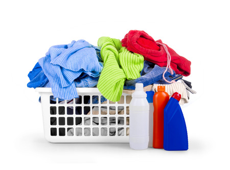 dropped: Clothes with detergent and in plastic basket dropped isolated on white