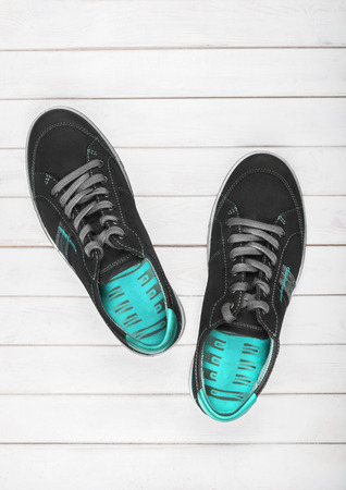 Black sneakers with blue lining on a white wooden background photo