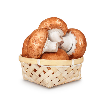 brown mushrooms in a light basket on an isolated white background