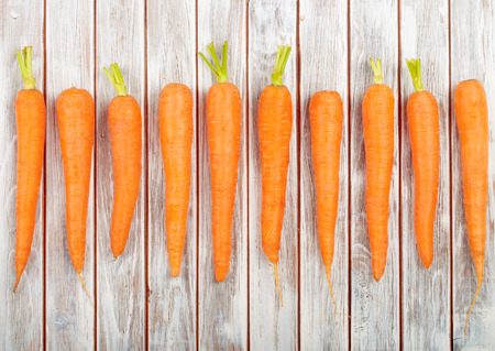 zanahoria: Zanahorias orgánicas frescas aisladas en el fondo de madera