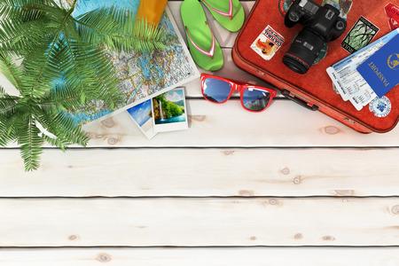 agencia de viajes: Concepto del recorrido. Tumbona, gafas de sol, mapa del mundo, zapatos de la playa, de protección solar, pasaportes, billetes de avión, cámara, palmas, pelota de playa, sombrero y vieja maleta roja para el recorrido en el fondo de madera. Foto de archivo