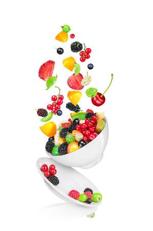 ensalada: cayendo ensalada de frutas con los ingredientes en el aire aislado en fondo blanco