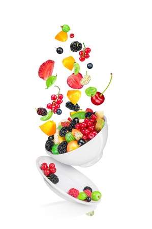 falling fruit salad with the ingredients in the air isolated on white background