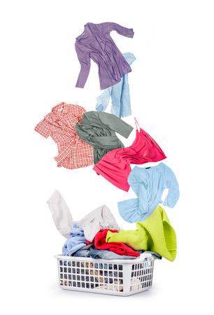 lavanderia: Servicio de lavandería en una cesta y la caída de la ropa - aislados en un fondo blanco Foto de archivo