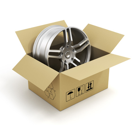 vulcanize: Open cardboard box with car rims on white background. Online store of auto parts. Stock Photo