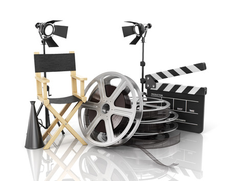 Video, movie, cinema concept. Light, film strip, reels, clapperboard and director chair on the white film background.