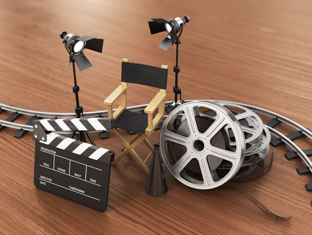filmroll: Video, movie, cinema concept. Light, film strip, reels, rails, clapperboard and director chair on the wood background.