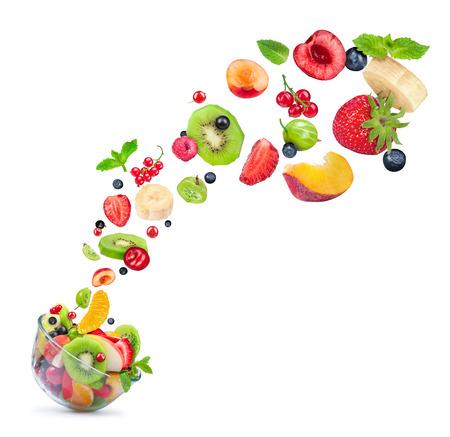 fruitsalade ingrediënten in de lucht in een glazen kom op een witte achtergrond