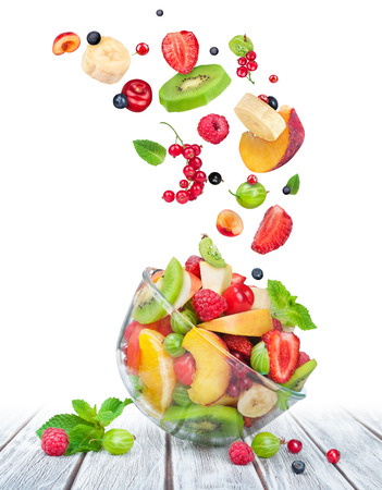fruit salad in glass bowl with ingredients in the air on white wooden table