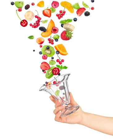 ensalada de frutas: la mano sostiene el tazón de vidrio de ensalada de frutas y los ingredientes en el aire sobre fondo blanco