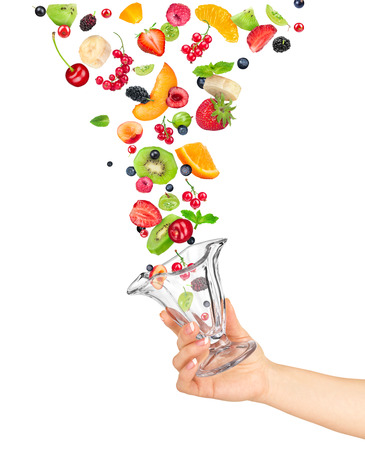 sliced fruit: the hand holds the glass bowl of fruit salad and the ingredients in the air isolated on white background