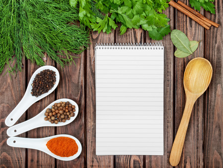 condiments: Spices recipe background. Variety of condiments with recipe sheet on old wooden table. Top view Stock Photo