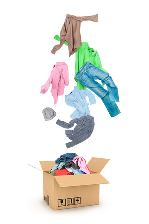 dirty clothes: Clothes Falling Into The Cardboard Box Isolated On White Stock Photo