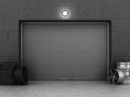 Garage building made of concrete with roller shutter doors, tires and rims