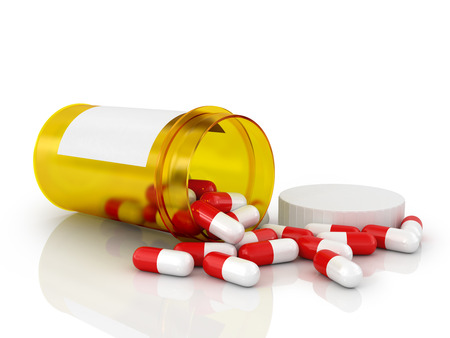 Pills spilling out of pill bottle isolated on white. Stock Photo