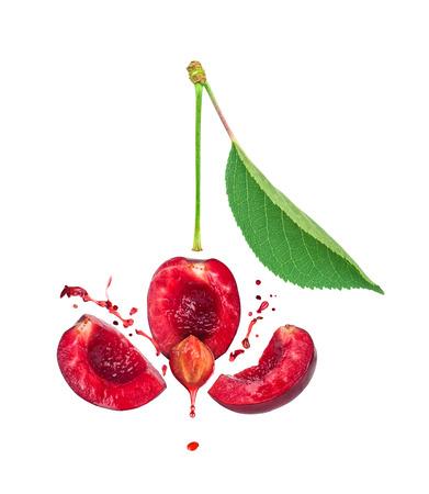 cereza: la explosión de cerezas durante tres rebanadas y un chorrito de jugo de cereza aislado en el fondo blanco Foto de archivo