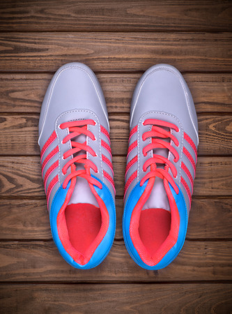 running shoes: Pair of running shoes laid on a wooden floor background Stock Photo