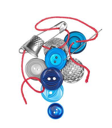 vestidos antiguos: hilo rojo con la aguja cose el bot�n azul aislado en fondo blanco