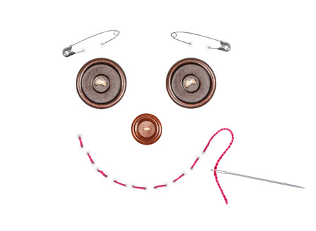 darning needle: picture made with buttons, pins, needle and thread