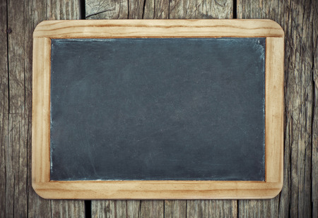 wooden frame: Empty vintage blackboard with wooden frame on a wooden backgroun