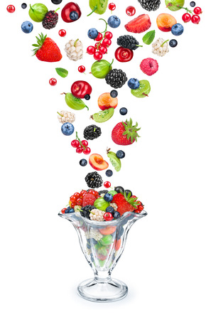 mixed berry falls into the ramekin with berry salad isolated on white background Stock Photo