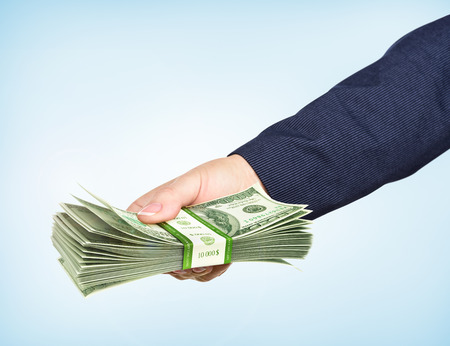 pack of dollars: Hand holds a pack of dollars on blue background. Take the money.