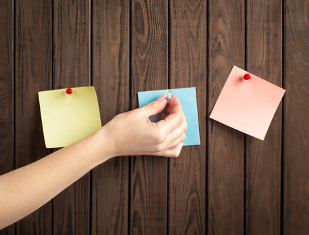 tack board: note papers with hand on wooden board Stock Photo