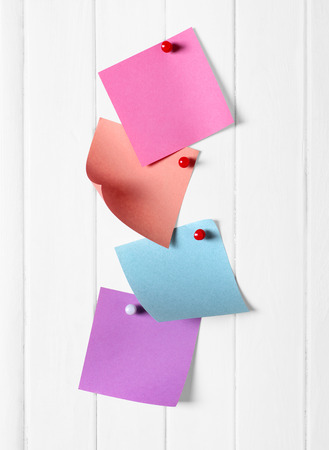 tack board: colored paper for notes on a white wooden background