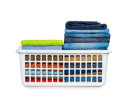 Laundry basket with folded clothes over white background Stock Photo