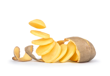 Peeled potatoes with the skin as a spiral pieces of potatoes fall in the air on white background