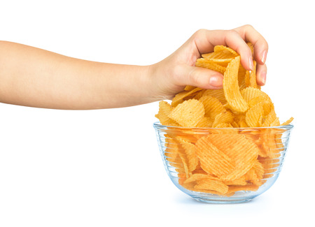 potato chips: hand takes a handful of potato chips from a glass bowl isolated on white background