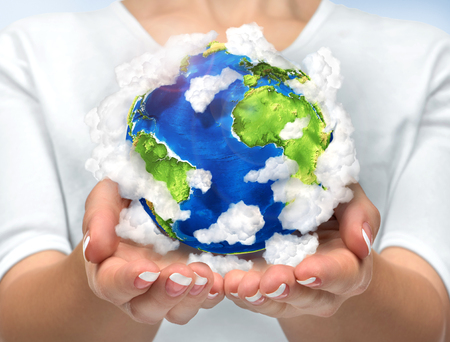 enviroment: Our planet in our hands. Open hands holding 3d planet earth with clouds. Concept of saving enviroment nature. Stock Photo