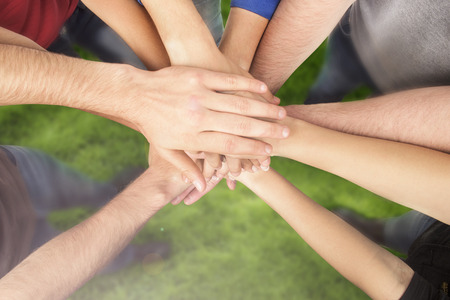 multiracial group of friends with hands in stack teamwork banco de