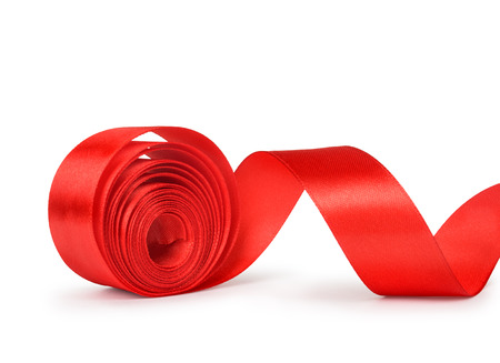 unwound: the unwound roll of red ribbon isolated on white background