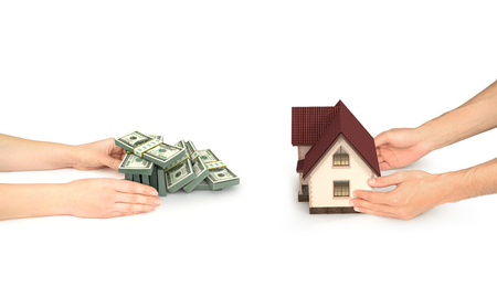 future earnings: real astate concept, hand with house and hands with dollars bills isolated
