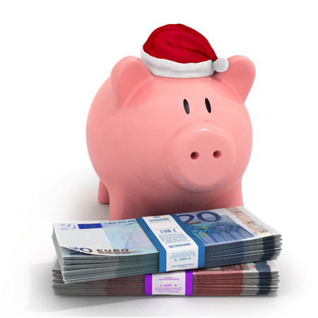 buying stock: Piggy bank in a Christmas hat with bundles of euro banknotes Stock Photo